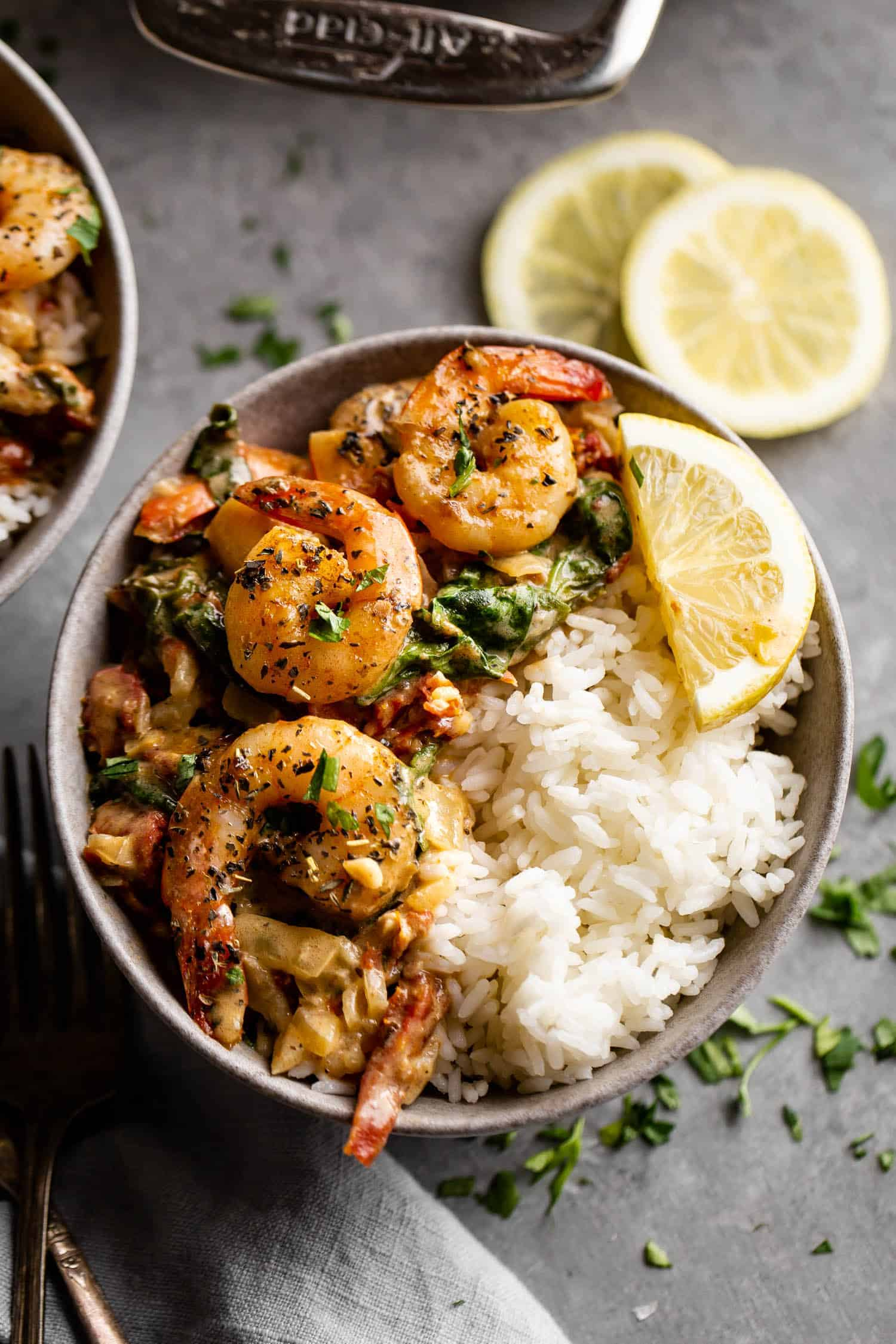 garlic shrimp in a bowl with white rice and lemon slices