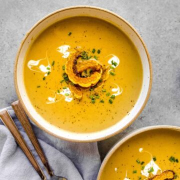 roasted delicata squash soup in a bowl with spoons on the side