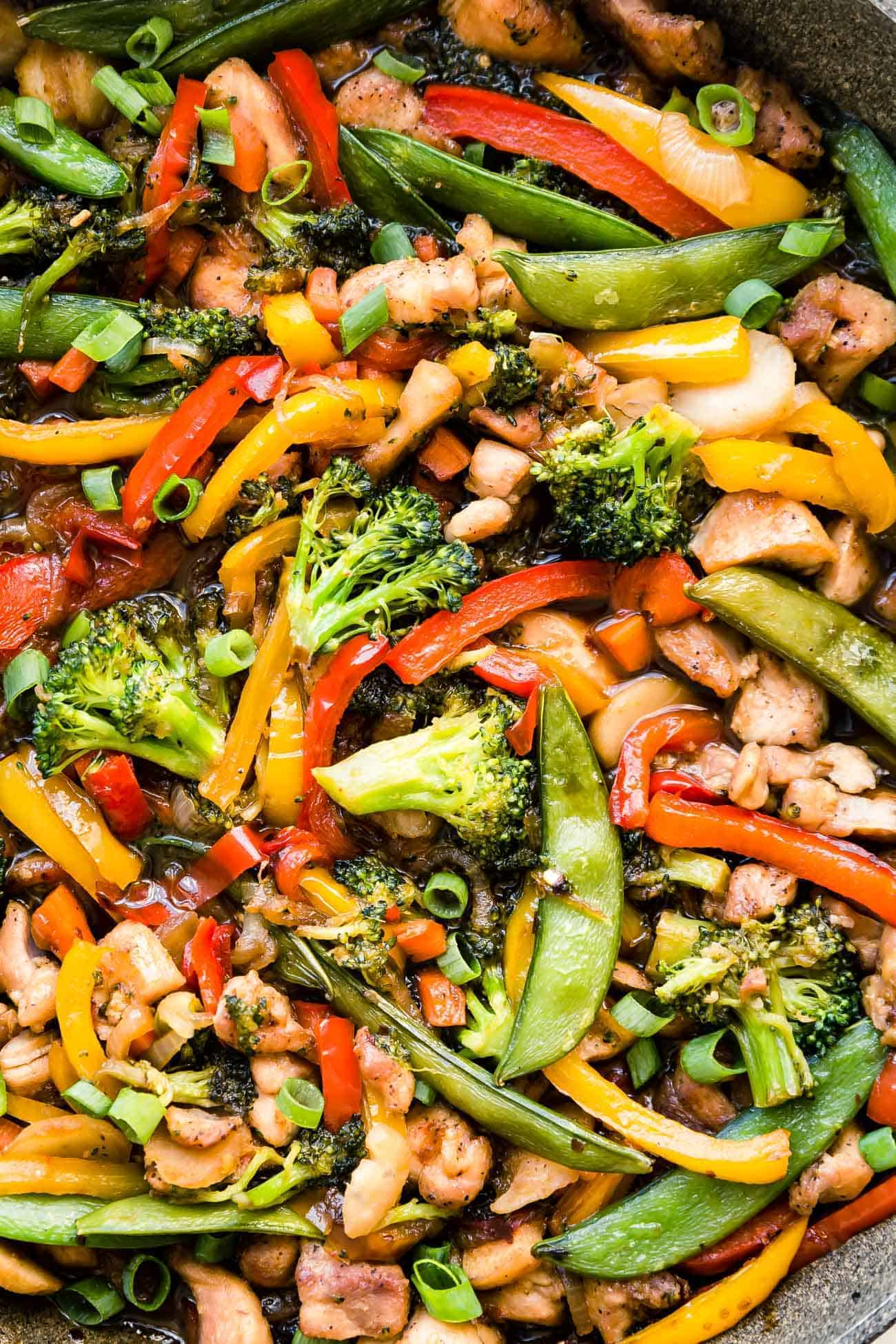 close of chicken stir fry with broccoli, bell peppers, snap peas and carrots