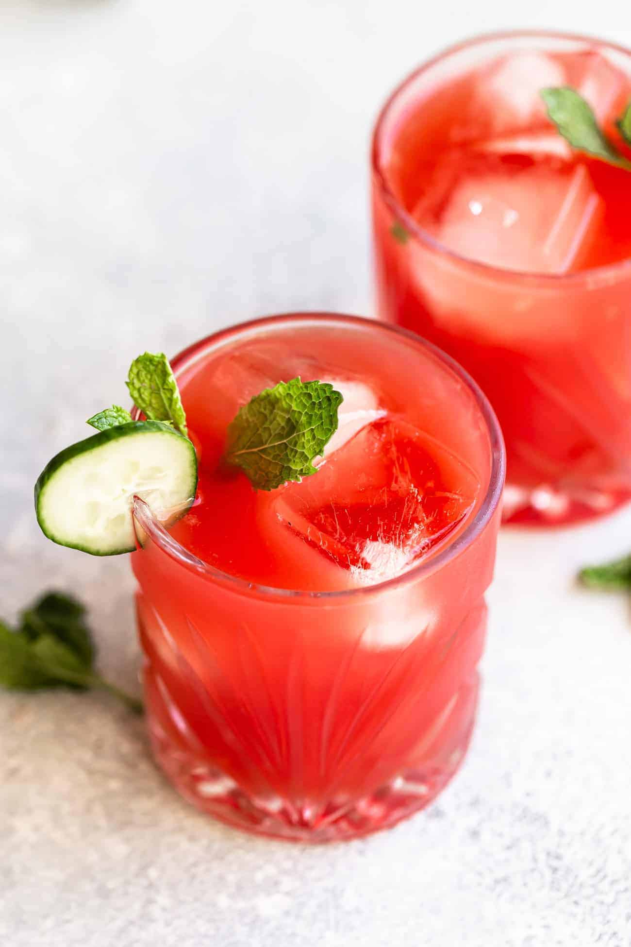 two watermelon cocktails in glasses with cucumber and mint