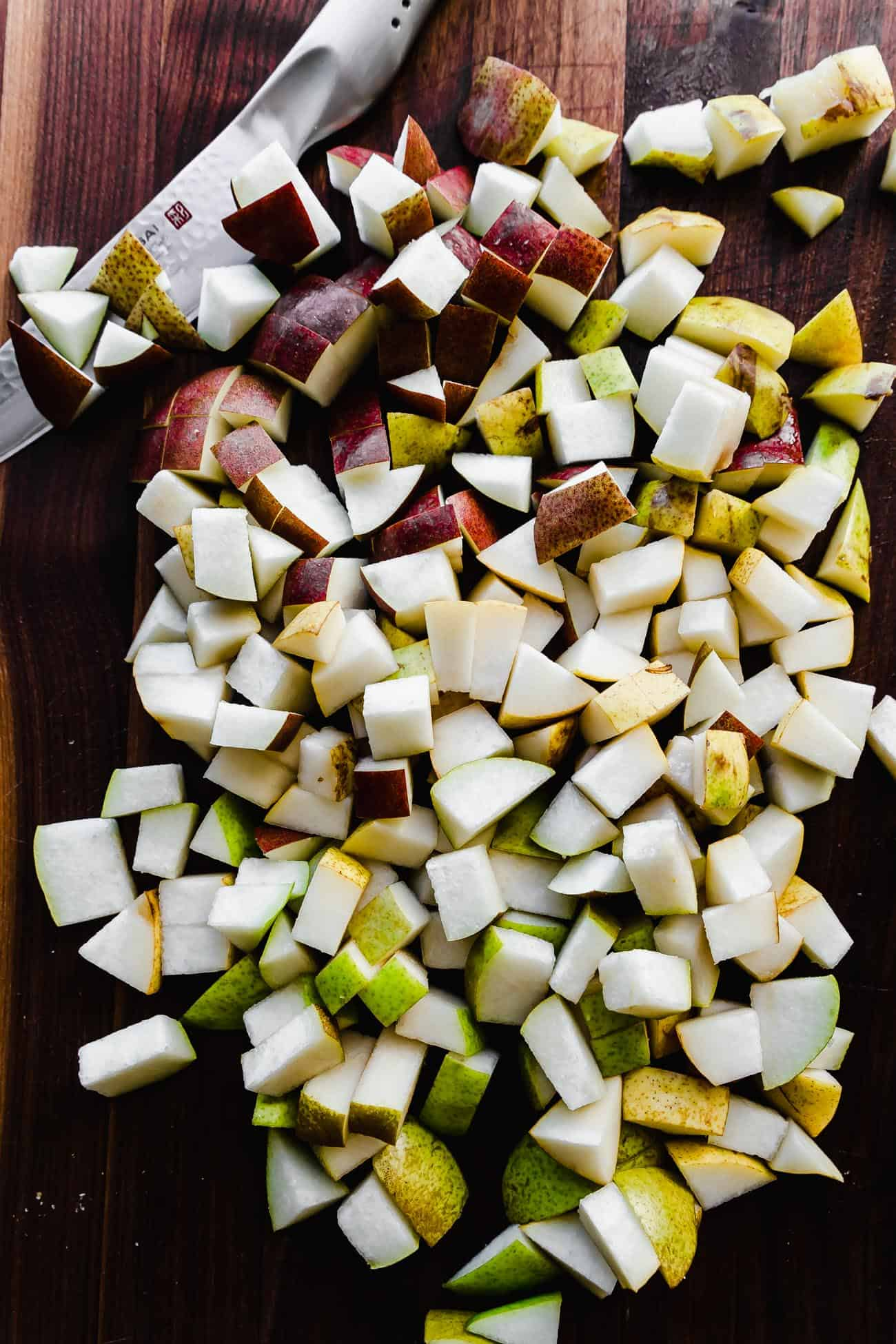 red and green pears chopped on a dark wood cutting board