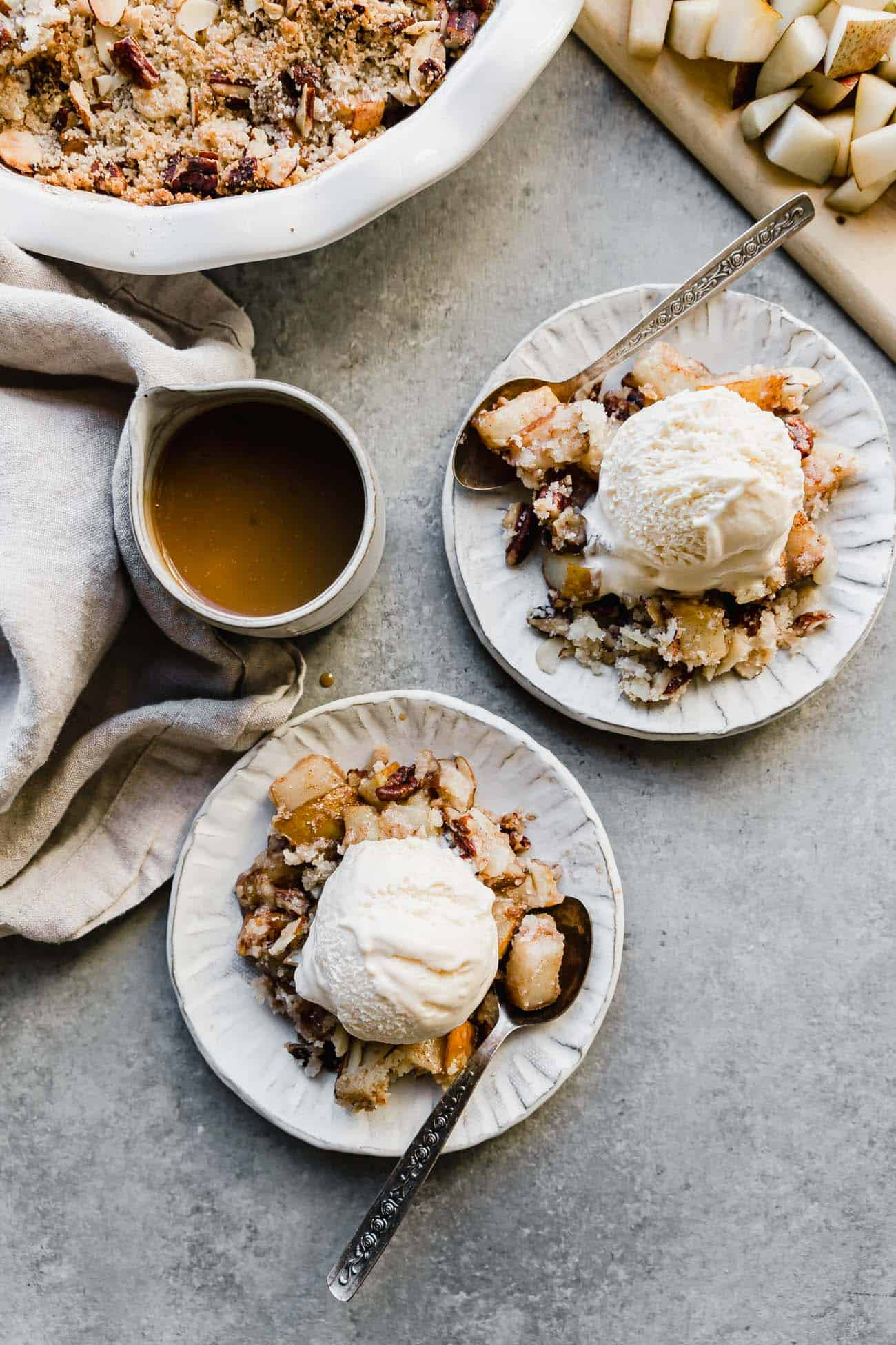 two plates of pear crisp with vanilla ice cream on top
